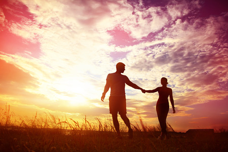 romantic sex: Silhouettes of a young couple lovers at sunset in rays of setting sun. people outdoors