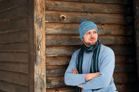 unshaven: handsome unshaven man in winter clothes standing near his house Stock Photo