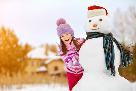 snowman: happy kid playing with snowman. funny little girl on a walk in the winter outdoors
