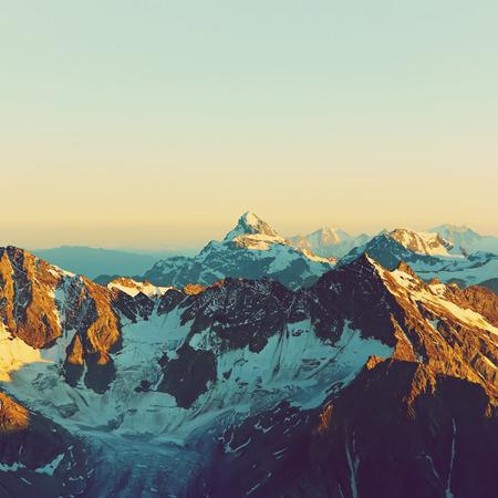 montañas nevadas: paisaje alpino con picos cubiertos por la nieve y las nubes. fondo natural de montaña Foto de archivo