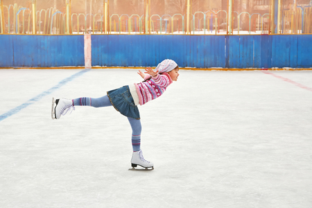 cute little girl in a hat and a sweater ice skating. child winter outdoors on ice rink