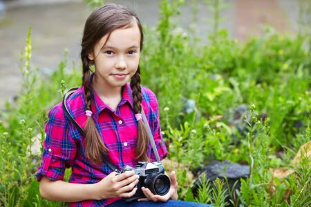 outside shooting: teenage girl with a camera. old photo camera. youth lifestyle