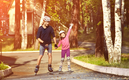 rollerskating: Dad with little daughter on the skates. two people skating. sports family rollerskating outdoor