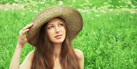 sexy female: beautiful dreaming woman in a hat in a summer park on a background of green grass. people outdoors