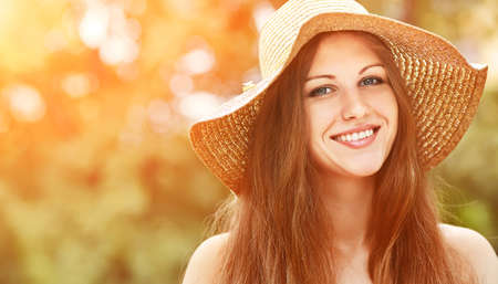 sexy glamour model: beautiful smiling dreaming woman in a hat in a summer park on a background of green grass. people outdoors Stock Photo