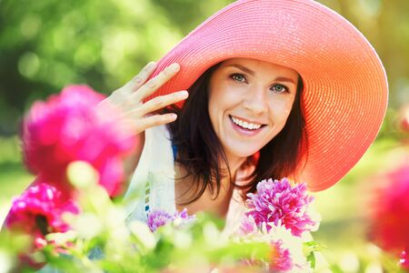 aged: outdoor closeup portrait of a beautiful middle aged woman. lady in a wide brimmed hat in the park with flowers Stock Photo