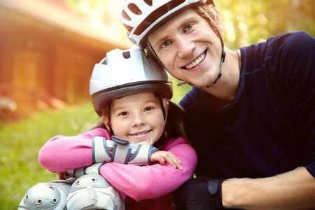 HAPPY FAMILY: retrato de un padre y su hija de deportes en un casco. Pap� con su peque�a hija en los patines