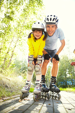 rollerblade: portrait of a sports dad and daughter in a helmet. Dad with his little daughter on the skates. two people rollerblade
