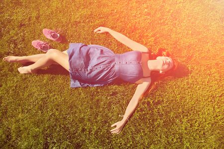 adult nude: redhead girl relaxing lying on the grass. woman relaxation outdoor Stock Photo