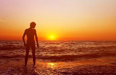 silueta masculina: silueta de un hombre feliz admira la puesta de sol sobre el mar. estilo de vida saludable. la libertad y la inspiración Foto de archivo