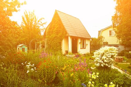 Wunderschönes rustikales Landhaus im üppigen Garten. Gartenblumen Standard-Bild