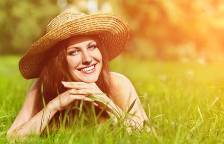 femme brune sexy: belle femme souriante r�ver dans un chapeau couch� sur l'herbe dans le parc et regarde de c�t� Banque d'images