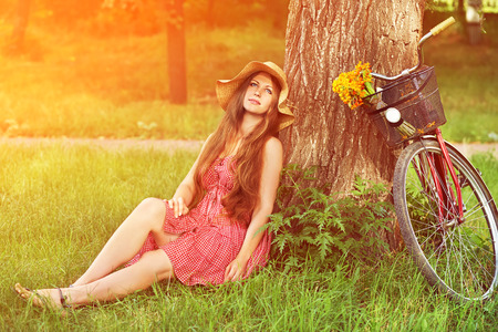 girl bike: young woman in a hat with a bike sitting in the park near the tree . Active people. Outdoors Stock Photo