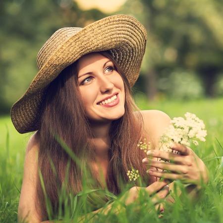 mooie glimlachende vrouw in een hoed die op het gras in een zomer park met een boeket van witte bloemen