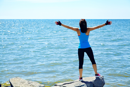 vastness: athletic woman on the background of the sea. freedom and a healthy lifestyle. harmonious person outdoors. the nature and vastness of the ocean. freedom Stock Photo