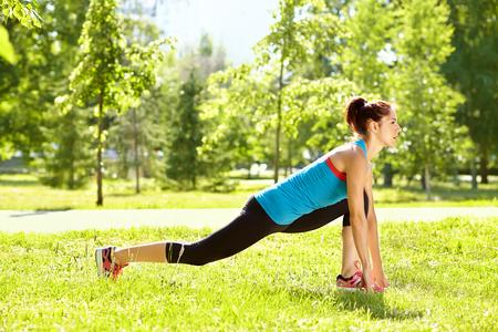 sportieve atletische vrouw op een gras achtergrond. buitensport. gezonde sport levensstijl. fitness, yoga Stockfoto