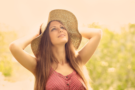 beautiful smile: beautiful smiling dreaming woman in a hat in a summer park. toning effect Stock Photo