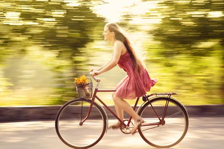 동작 흐림 효과. 젊은 여자 드레스에 여름 공원에서 자전거를 타고. 활동적인 사람들. 옥외 스톡 콘텐츠