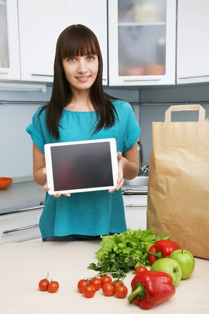 uses a computer: young housewife uses a tablet computer in the kitchen. woman following recipe cooking vegetables on digital tablet. online food shopping
