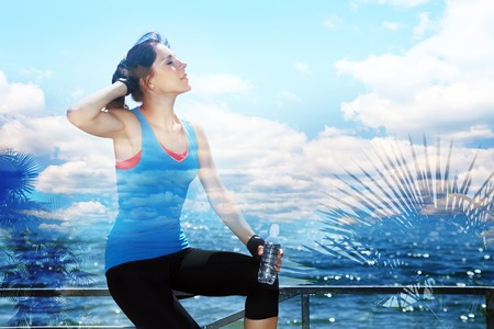 vastness: double exposure of sporty woman with a water bottle in training. outdoor sports. healthy sport lifestyle. travel, nature and vastness of the ocean Stock Photo