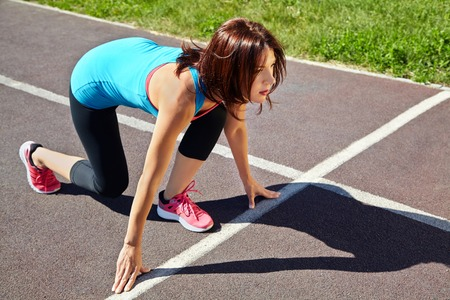 jogging track: athletic woman at the starting line athlete running on jogging track at the stadium. jogging outdoors Stock Photo