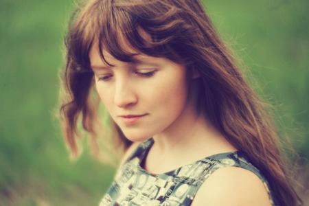 blurring: photo with artistic blurring and blur effect. special defocused effect. vintage toning. film retro style. outdoor portrait of a young beautiful woman. soft focus
