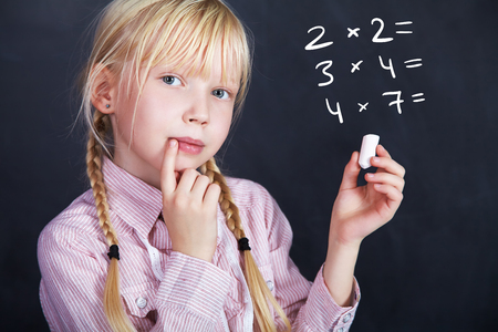 diligent: schoolchild with chalk in hand on a background of a blackboard. School and education Stock Photo