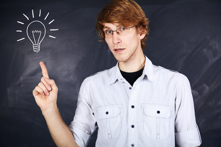 indicative: pensive young man with glasses pointing finger up on the background of the board