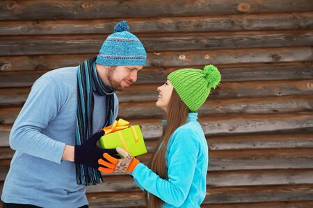 gives: Young happy couple in love outdoors in the winter. a man gives gift to a woman