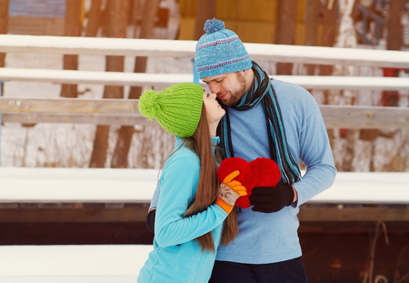 Young kissing couple in love outdoors in the winter with a red heart in hands. valentines day Stock Photo