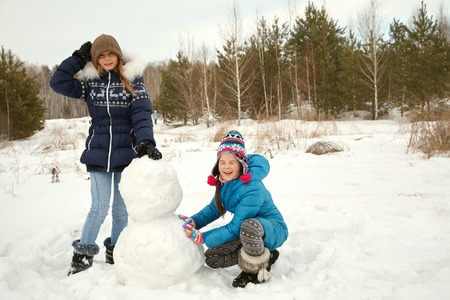 twofunny girls building a snowman in the winter