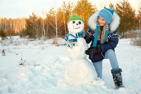happy kid playing with snowman in the winter outdoors
