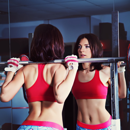 sporty attractive fitness woman with barbell in gym