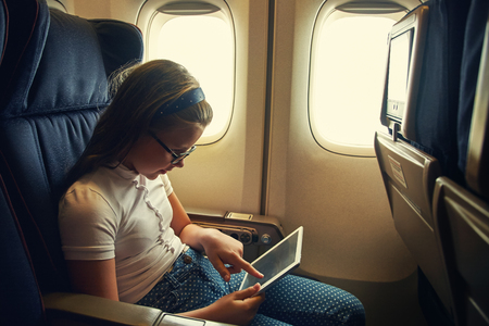 little girl in chair on board an airplane with tablet computer