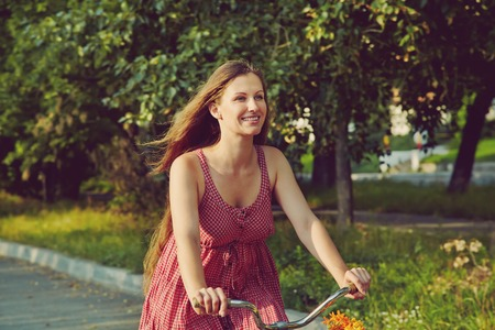 young woman in a dress rides a bike in summer park