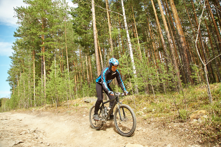 cyclist riding a mountain bike along forest road Stock fotó