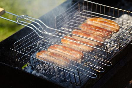 红香肠是在炭火上烤的。在冒烟的烤架上烧烤
