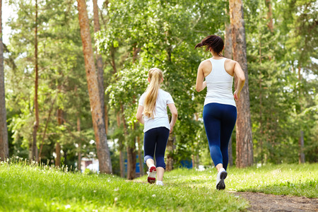 running mother and daughter. woman and child jogging in a park. outdoor sports and fitness family