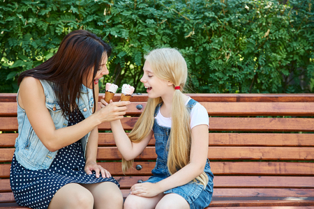 mother and daughter eating ice cream in a park sitting on a bench
