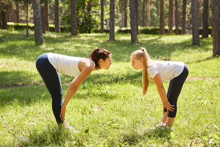 sporty mother and daughter. woman and child training in a park. sports and fitness family 写真素材
