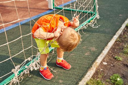 little boy on playground with a grid of football gate Standard-Bild - 123196997