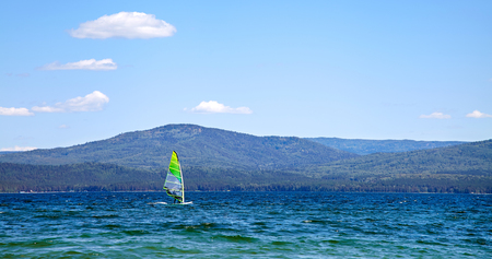 windsurfer on a mountain lake in good weather on a background of blue sky