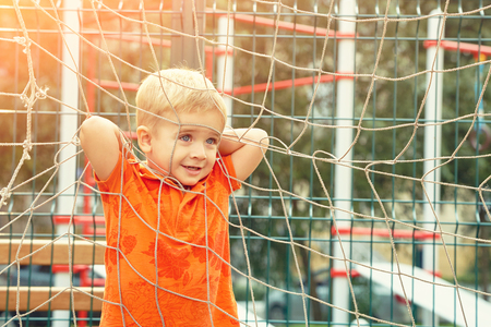 funny little boy on playground with a grid of football gate Reklamní fotografie
