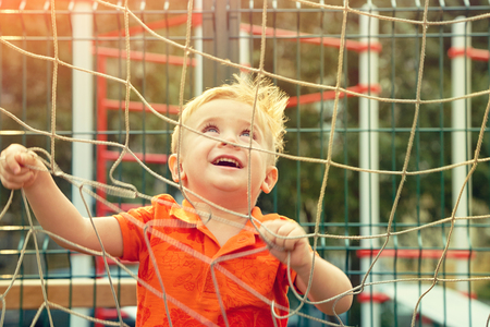 funny little boy on playground with a grid of football gate Standard-Bild - 123197114