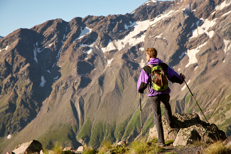 climber on trail in the mountains. a man with a backpack in hike