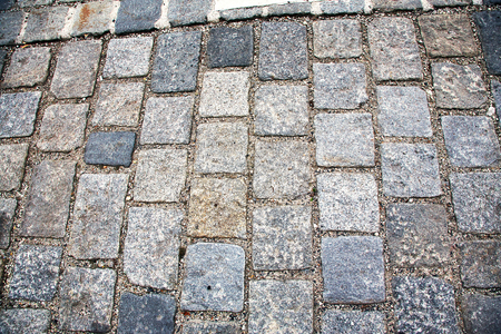 Road paved with paving stones. Cobbles background.