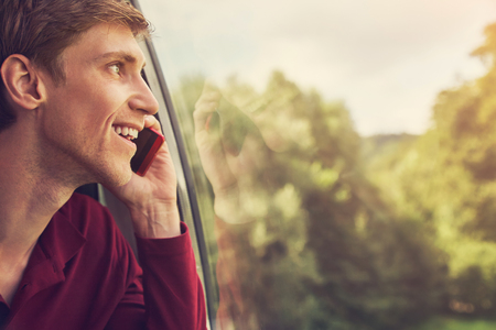 handsome young man talking on mobile phone looking out a window.