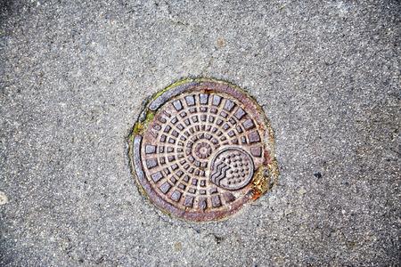 Small sewer hatch in asphalt road. roadside metal detail.