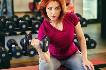 sportliche Fitnessfrau mit Hanteln im Fitnessstudio. trainierter weiblicher Körper