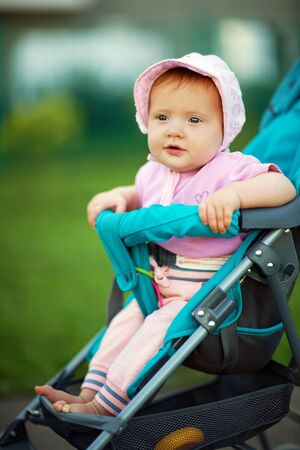 little girl in a stroller. baby for a walk in a pram. child in summer outdoors 写真素材